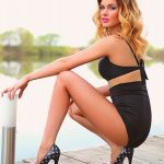 Call girl Ankara is sitting near the water surface dressed in very stylish black dress and the same-colored and styled bra