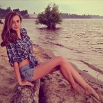 One of the Ukrainian girls Ankara Alina is sitting on a wooden log on the seashore and we see it is high tide now as the branches of a tree in the background are submerged in water